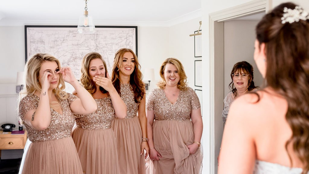 emotional bridesmaids wearing rose gold dresses seeing bride for the first time