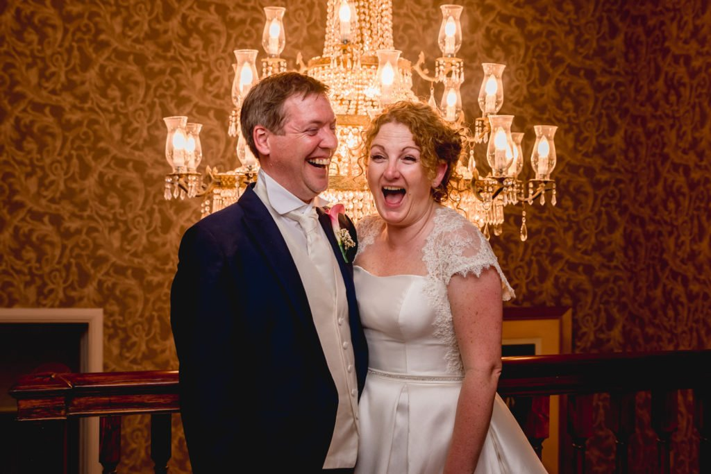 Bride and groom laughing together in front of a chandelier at Stoke Place