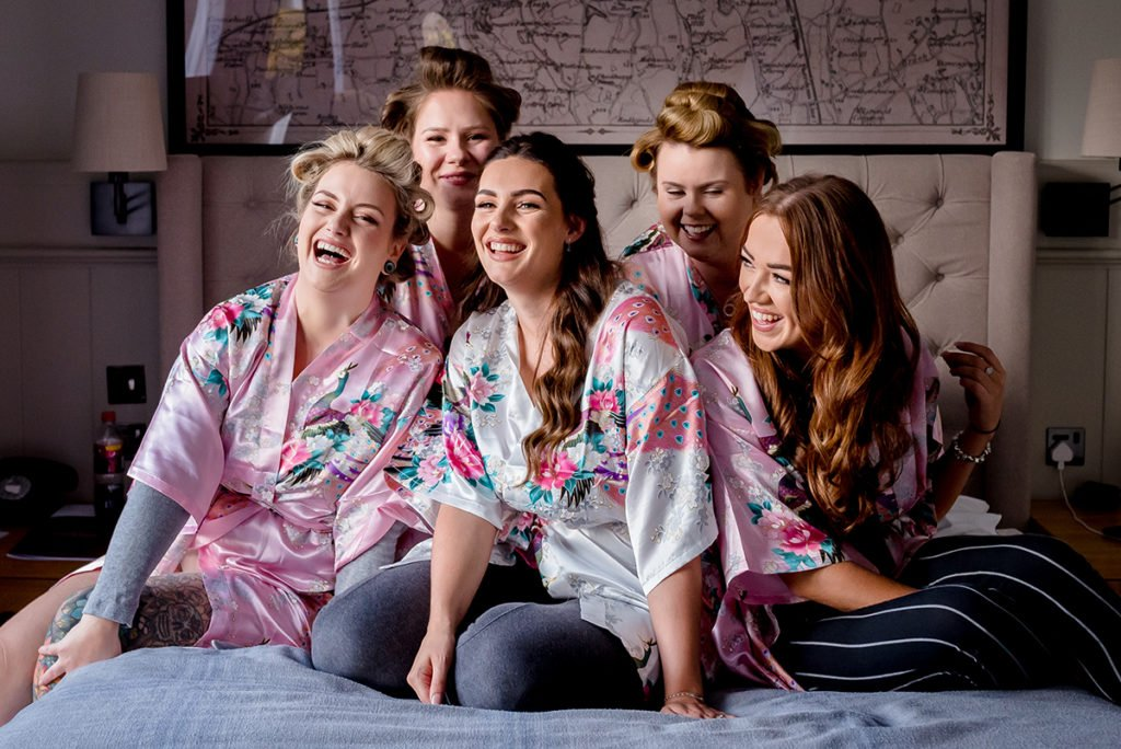 bride laughing with her bridesmaids wearing matching dressing gowns