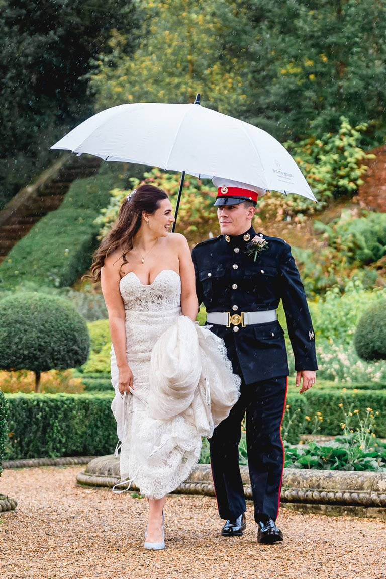 bride and groom laughing walking through the rain holding an umbrella