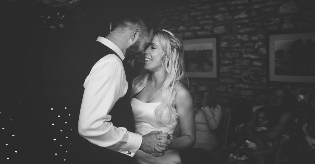 black and white photo of bride and grooms first dance together