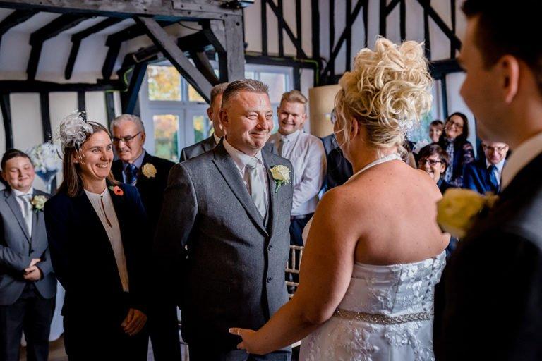Groom smiling at Bride during ceremony The Warren Estate in Maldon