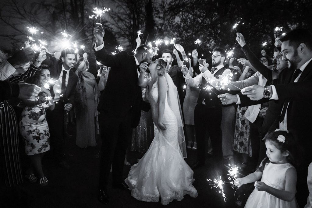 black and white portrait of bride and groom kissing surrounded by sparklers at Norfolk Mead Hotel