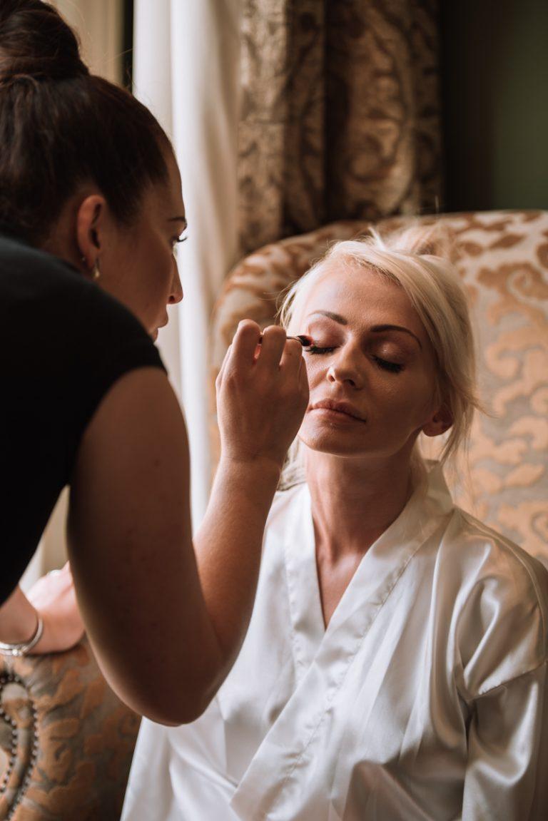 bride having her makeup applied before her ceremony