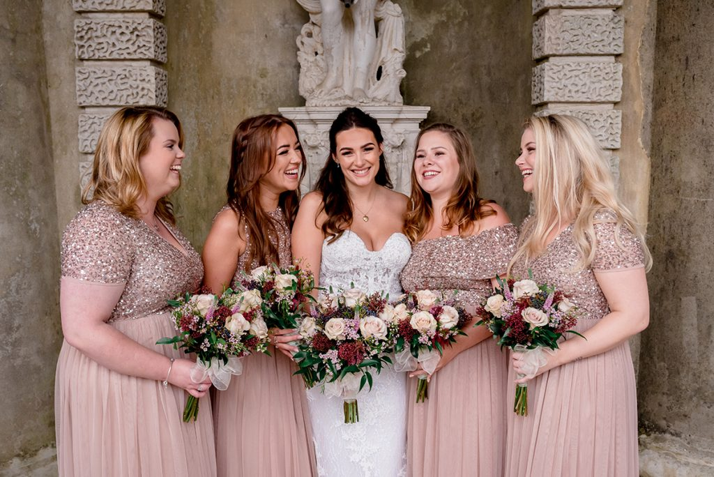 bride laughing with her bridesmaids in rose gold dresses Essex wedding