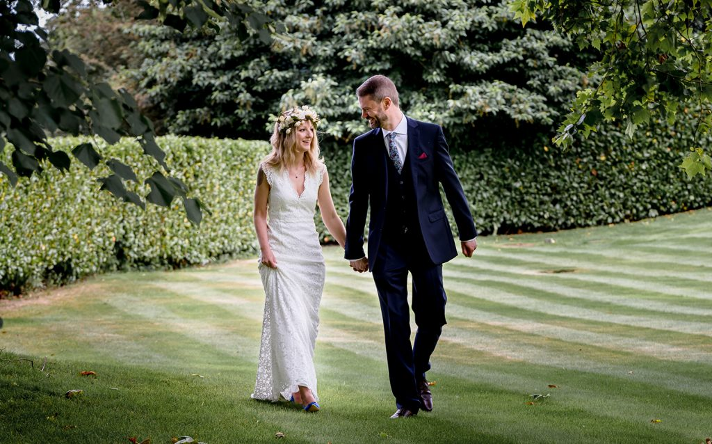 bride and groom walking across grass Le Talbooth Essex