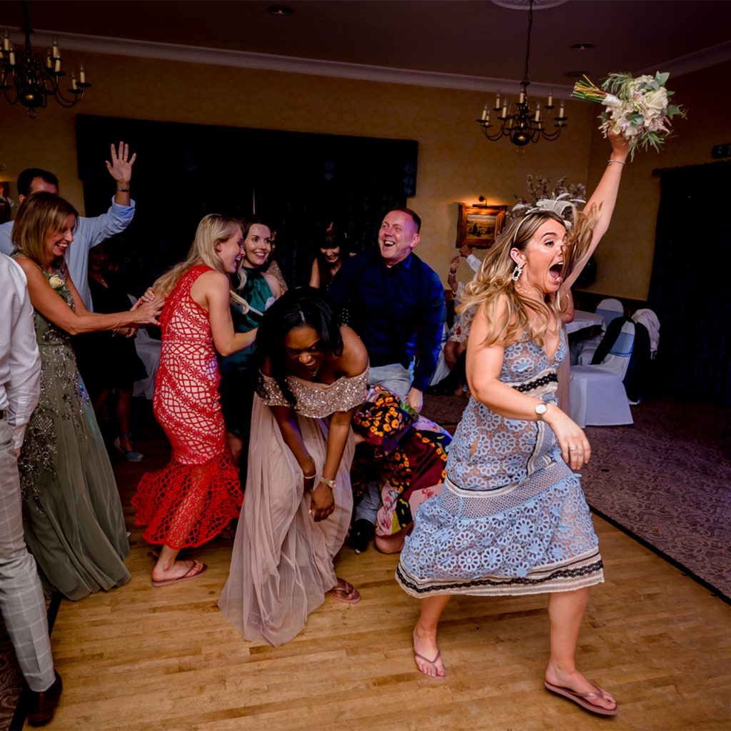 wedding guest ecstatic she has caught the brides bouquet at Stower Grange in Norfolk