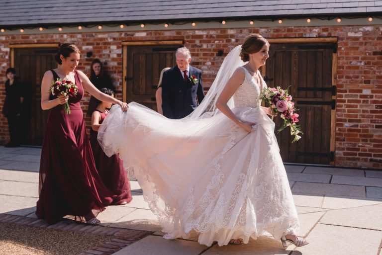 bridesmaids carrying brides dress train to wedding ceremony at Apton Hall in Essex