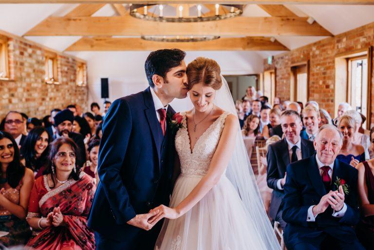 groom kissing brides forehead during wedding ceremony at Apton Hall Essex