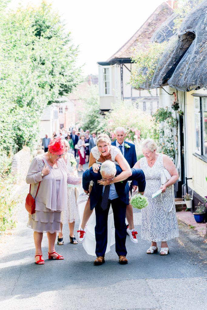 groom giving piggyback to bride at wedding at Hedingham Castle
