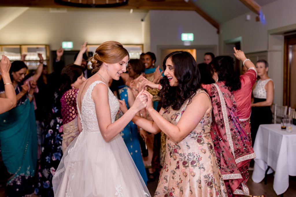 bride dancing with sister in law at Indian Essex wedding