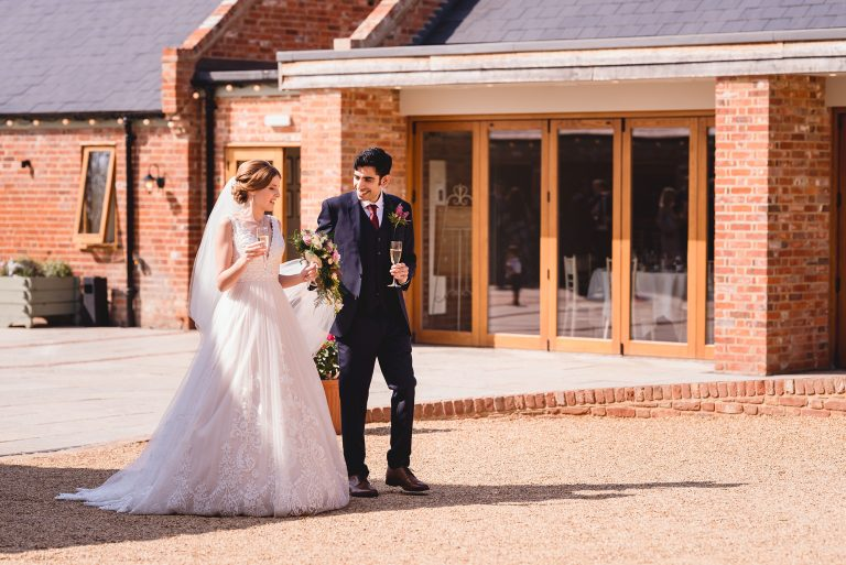 bride and groom drinking champagne walking through Apton Hall in Essex