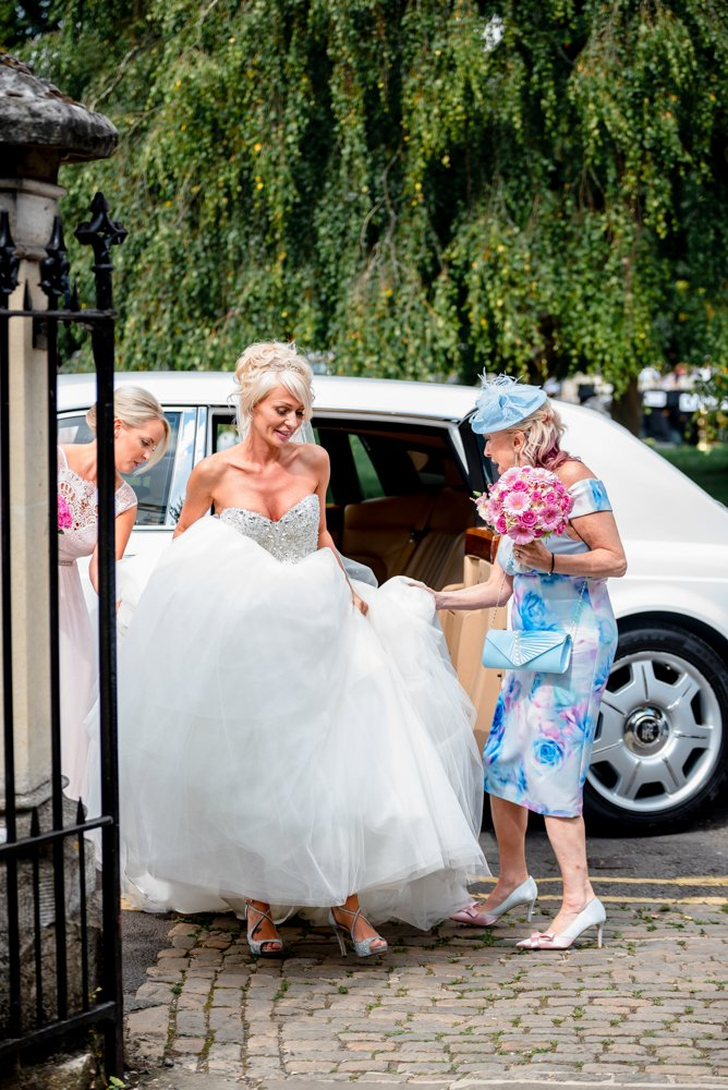 bride getting out of wedding car at Stoke Place