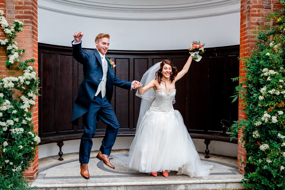 bride and groom jumping and laughing