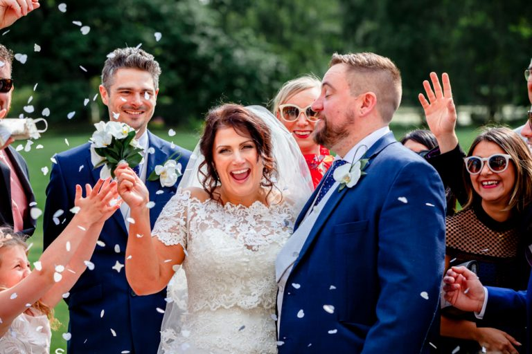bride grooming laughing covered in confetti at Stoke Place