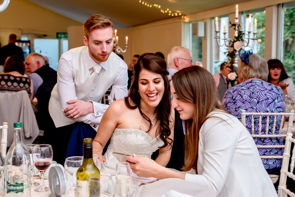 bride and groom laughing with wedding guest