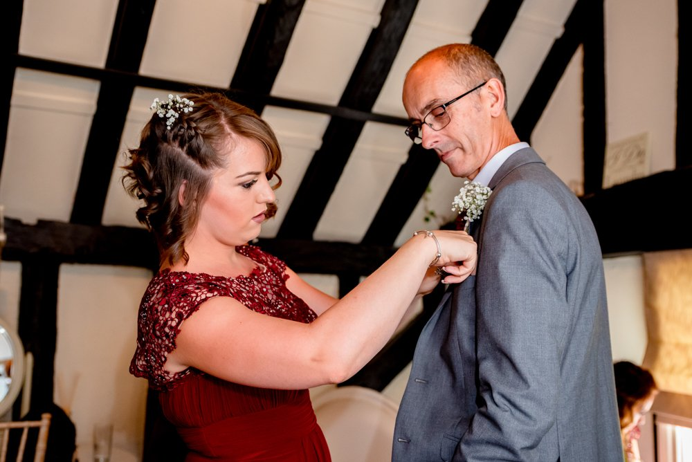 bridesmaid fixing buttonhole at The Warren Estate in Essex
