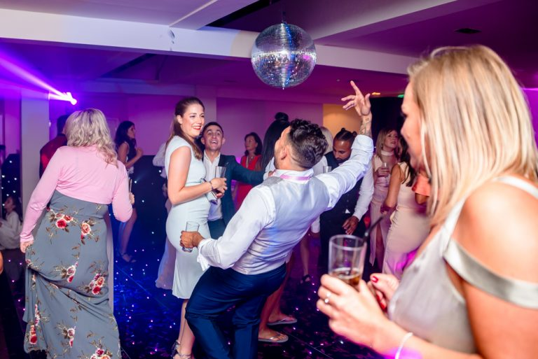 Usher signing and dancing with guests at wedding reception Stoke Place