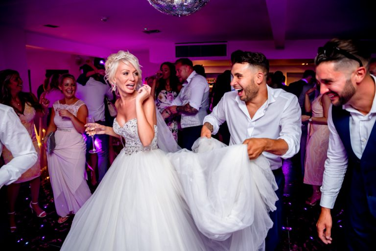 best man holding brides dress while dancing at Stoke Place