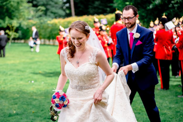 groom carrying brides wedding dress across grass