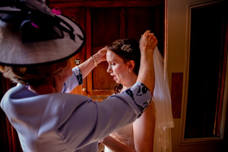 mother of the bride fixing brides veil