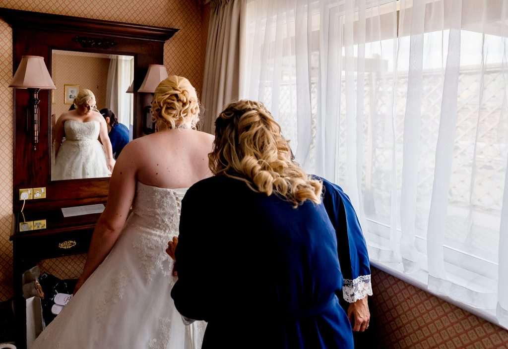 bridesmaid lacing up the back of brides dress at Best Western Marks Tye