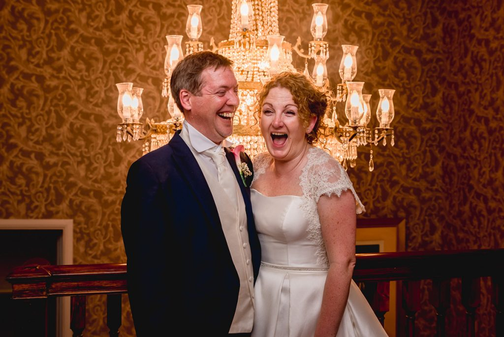 bride and groom laughing together by chandelier at Stoke Place