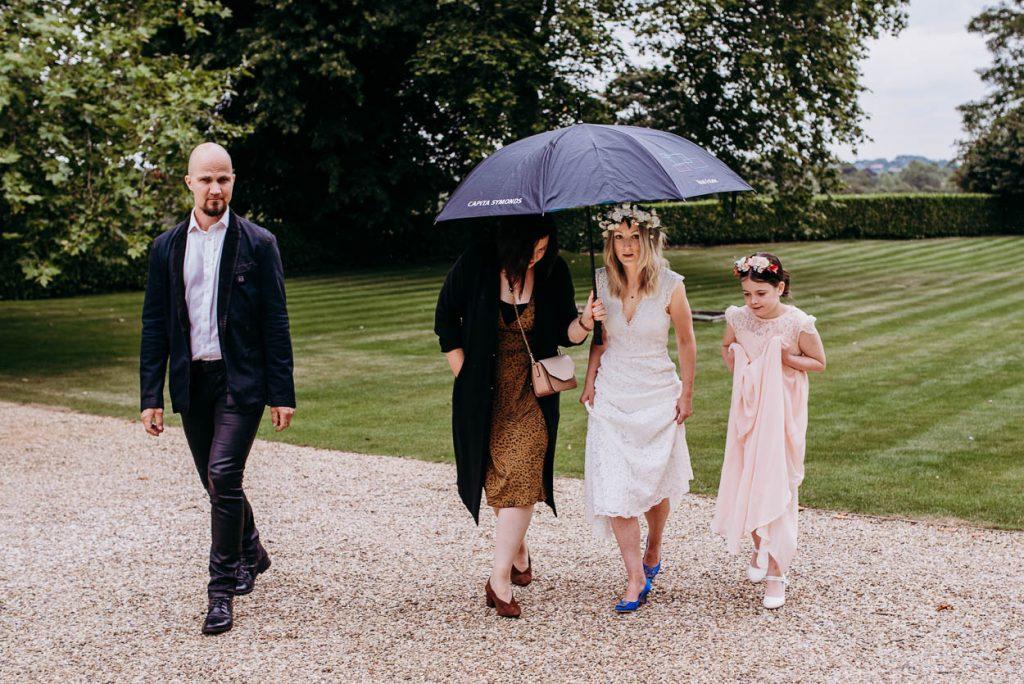bride walking through the rain Maison Talbooth Essex wedding photography
