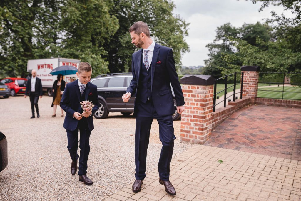 Groom with his son walking in to Maison Talbooth Essex